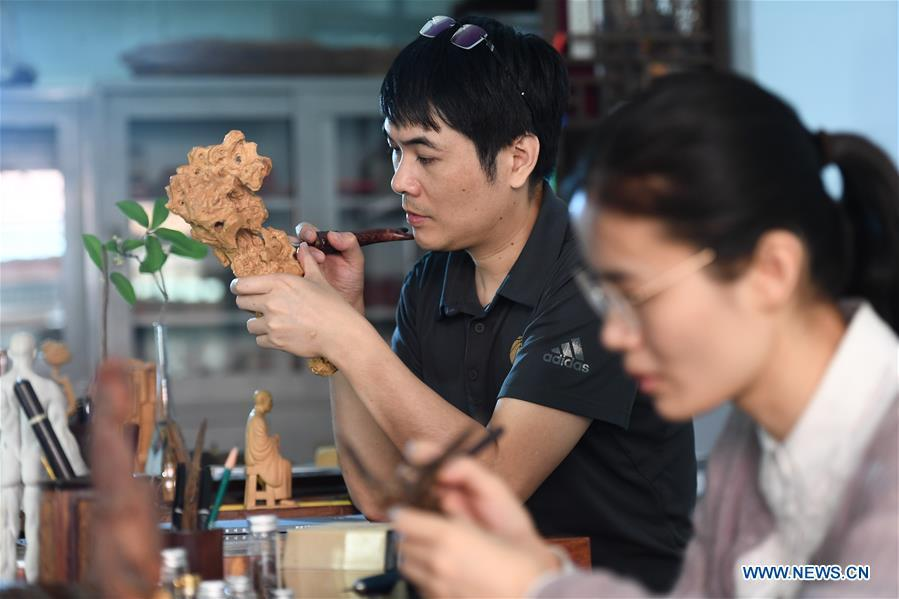 Lin Jianjun (L) and Chen Qin make wood carving at their studio in Putian, southeast China\'s Fujian Province, Oct. 24, 2018. Lin Jianjun, who learnt wood carving at the age of 16, has studied the making skill of this traditional artwork for more than 20 years. In 2014, Lin got married with Chen Qin. The wife was influenced by her husband and got interested in wood carving. She developed the wood carving by combining a traditional skill to make wood carving inlaid with gold and silver. The couple meanwhile try to promote the Putian wood carving by giving lessons, instructing apprentices and displaying their works to the public. In 2018, Lin was appointed as the inheritor of the wood carving skill, a provincial-level intangible cultural heritage. (Xinhua/Zhang Guojun)
