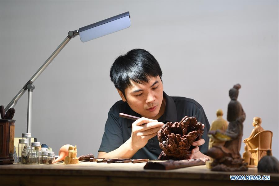 Lin Jianjun makes wood carving at a studio in Putian, southeast China\'s Fujian Province, Oct. 23, 2018. Lin Jianjun, who learnt wood carving at the age of 16, has studied the making skill of this traditional artwork for more than 20 years. In 2014, Lin got married with Chen Qin. The wife was influenced by her husband and got interested in wood carving. She developed the wood carving by combining a traditional skill to make wood carving inlaid with gold and silver. The couple meanwhile try to promote the Putian wood carving by giving lessons, instructing apprentices and displaying their works to the public. In 2018, Lin was appointed as the inheritor of the wood carving skill, a provincial-level intangible cultural heritage. (Xinhua/Jiang Kehong)