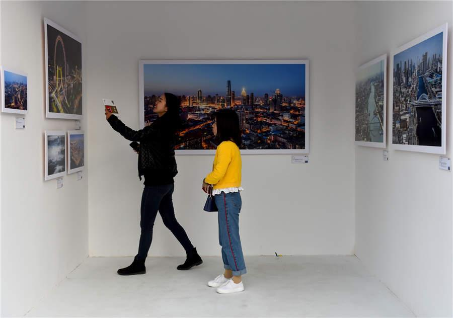 Visitors look at aerial photography works displayed at Photo Beijing 2018 in Beijing, Oct. 20, 2018.  (Photo/Xinhua)