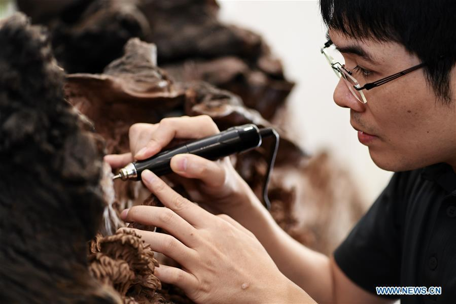 Lin Jianjun makes wood carving at a studio in Putian, southeast China\'s Fujian Province, Oct. 23, 2018. Lin Jianjun, who learnt wood carving at the age of 16, has studied the making skill of this traditional artwork for more than 20 years. In 2014, Lin got married with Chen Qin. The wife was influenced by her husband and got interested in wood carving. She developed the wood carving by combining a traditional skill to make wood carving inlaid with gold and silver. The couple meanwhile try to promote the Putian wood carving by giving lessons, instructing apprentices and displaying their works to the public. In 2018, Lin was appointed as the inheritor of the wood carving skill, a provincial-level intangible cultural heritage. (Xinhua/Zhang Guojun)