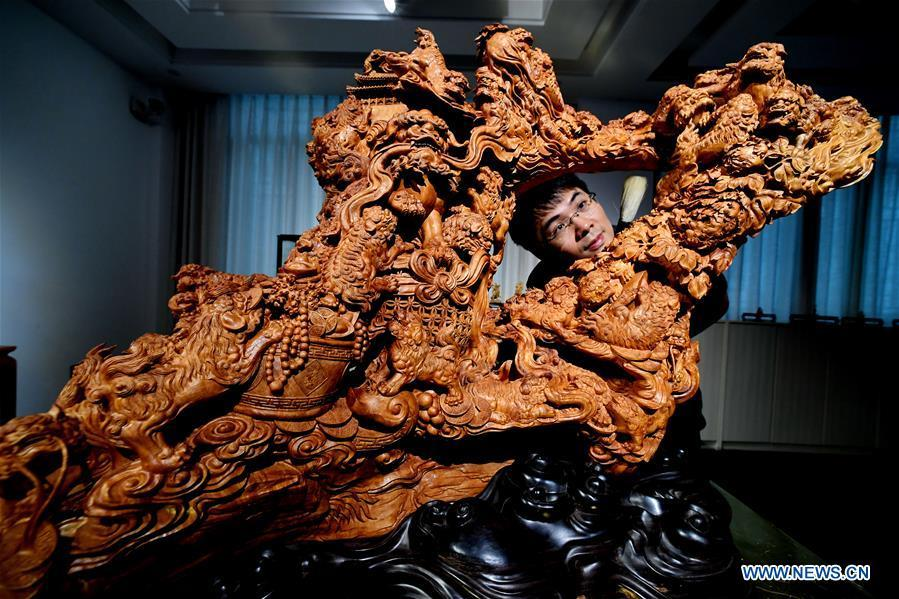 Lin Jianjun cleans his wood carving at a studio in Putian, southeast China\'s Fujian Province, Oct. 23, 2018. Lin Jianjun, who learnt wood carving at the age of 16, has studied the making skill of this traditional artwork for more than 20 years. In 2014, Lin got married with Chen Qin. The wife was influenced by her husband and got interested in wood carving. She developed the wood carving by combining a traditional skill to make wood carving inlaid with gold and silver. The couple meanwhile try to promote the Putian wood carving by giving lessons, instructing apprentices and displaying their works to the public. In 2018, Lin was appointed as the inheritor of the wood carving skill, a provincial-level intangible cultural heritage. (Xinhua/Zhang Guojun)