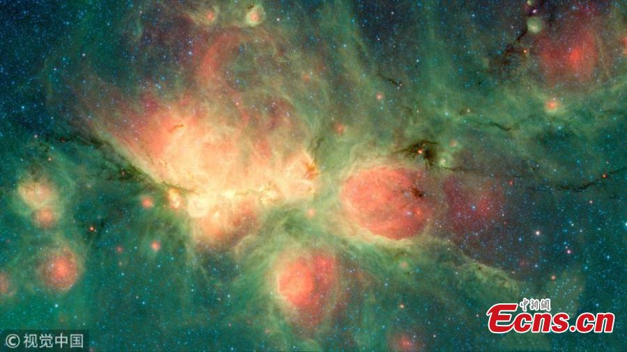 This image from NASA\'s Spitzer Space Telescope shows the Cat\'s Paw Nebula, so named for the large, round features that create the impression of a feline footprint. The nebula is a star-forming region in the Milky Way galaxy, located in the constellation Scorpius. Estimates of its distance from Earth range from about 4,200 to about 5,500 light-years. Framed by green clouds, the bright red bubbles are the dominant feature in the image, which was created using data from two of Spitzer\'s instruments. After gas and dust inside the nebula collapse to form stars, the stars may in turn heat up the pressurized gas surrounding them, causing it to expand into space and create bubbles.(Photo/VCG)
