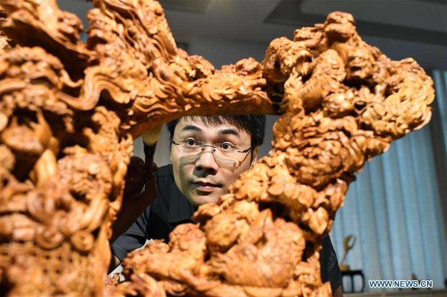 Lin Jianjun cleans his wood carving at a studio in Putian, southeast China\'s Fujian Province, Oct. 23, 2018. Lin Jianjun, who learnt wood carving at the age of 16, has studied the making skill of this traditional artwork for more than 20 years. In 2014, Lin got married with Chen Qin. The wife was influenced by her husband and got interested in wood carving. She developed the wood carving by combining a traditional skill to make wood carving inlaid with gold and silver. The couple meanwhile try to promote the Putian wood carving by giving lessons, instructing apprentices and displaying their works to the public. In 2018, Lin was appointed as the inheritor of the wood carving skill, a provincial-level intangible cultural heritage. (Xinhua/Jiang Kehong)