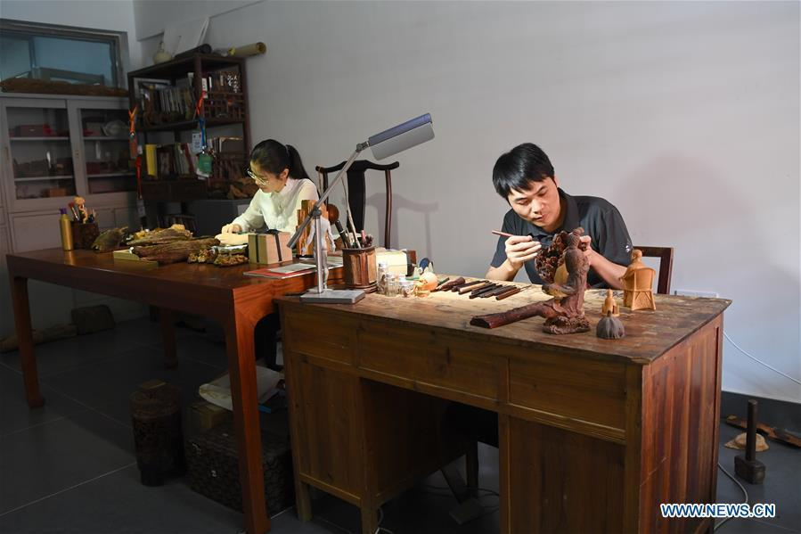Lin Jianjun (R) and Chen Qin make wood carving at their studio in Putian, southeast China\'s Fujian Province, Oct. 23, 2018. Lin Jianjun, who learnt wood carving at the age of 16, has studied the making skill of this traditional artwork for more than 20 years. In 2014, Lin got married with Chen Qin. The wife was influenced by her husband and got interested in wood carving. She developed the wood carving by combining a traditional skill to make wood carving inlaid with gold and silver. The couple meanwhile try to promote the Putian wood carving by giving lessons, instructing apprentices and displaying their works to the public. In 2018, Lin was appointed as the inheritor of the wood carving skill, a provincial-level intangible cultural heritage. (Xinhua/Jiang Kehong)