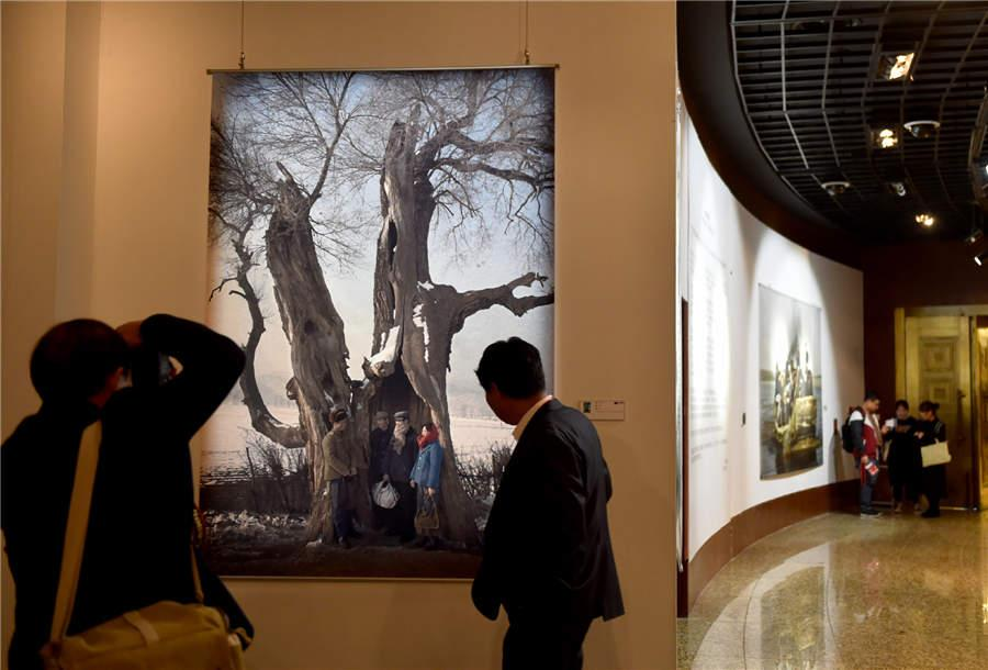 Visitors look at a documentary photography work displayed at Photo Beijing 2018 in Beijing, Oct. 20, 2018. (Photo/Xinhua)