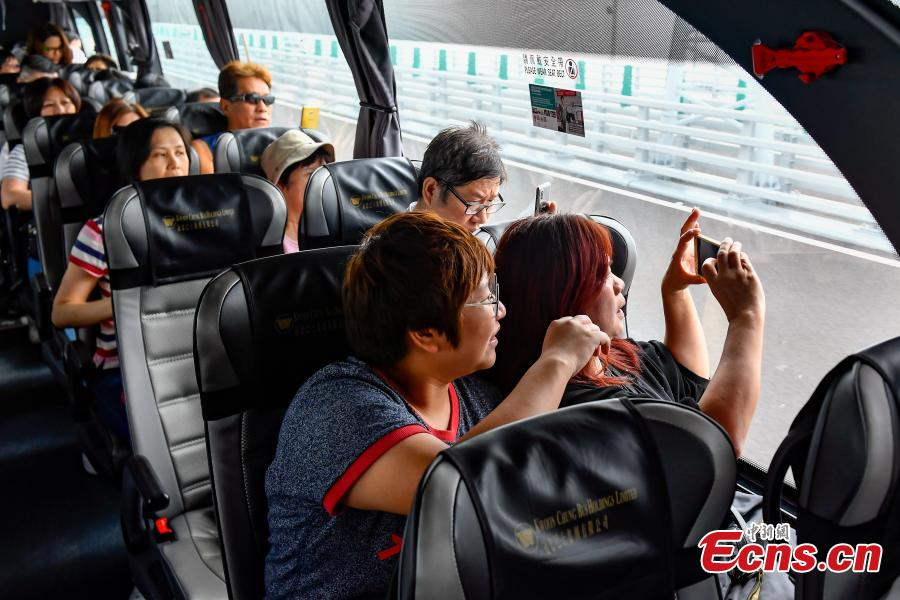 <?php echo strip_tags(addslashes(Passengers inside a coach take photos of the Zhuhai-Hong Kong-Macao Bridge. (Photo: China News Service/ Chen Jimin))) ?>