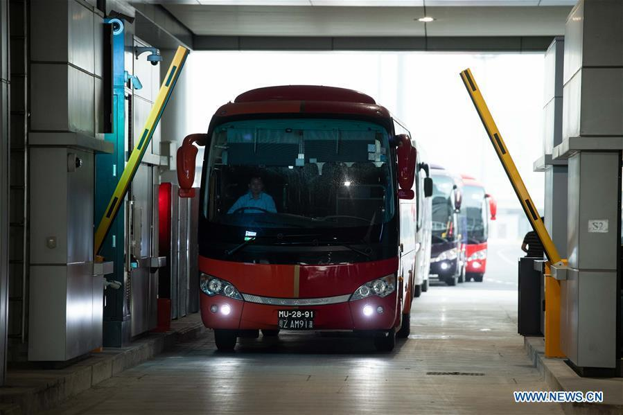 A shuttle bus goes through the Macao port of the Hong Kong-Zhuhai-Macao Bridge, Oct. 24, 2018. The Hong Kong-Zhuhai-Macao bridge, the world\'s longest cross-sea bridge, opened to public traffic at 9 a.m. Wednesday. (Xinhua/Cheong Kam Ka)