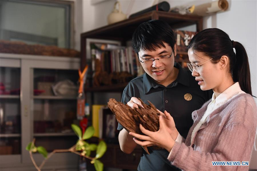 Lin Jianjun (L) and Chen Qin discuss the design of wood carving ornament at their studio in Putian, southeast China\'s Fujian Province, Oct. 24, 2018. Lin Jianjun, who learnt wood carving at the age of 16, has studied the making skill of this traditional artwork for more than 20 years. In 2014, Lin got married with Chen Qin. The wife was influenced by her husband and got interested in wood carving. She developed the wood carving by combining a traditional skill to make wood carving inlaid with gold and silver. The couple meanwhile try to promote the Putian wood carving by giving lessons, instructing apprentices and displaying their works to the public. In 2018, Lin was appointed as the inheritor of the wood carving skill, a provincial-level intangible cultural heritage. (Xinhua/Jiang Kehong)