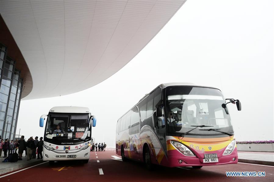Shuttle buses arrive at the Zhuhai port of the Hong Kong-Zhuhai-Macao Bridge, in Zhuhai, south China\'s Guangdong Province, Oct. 24, 2018. The Hong Kong-Zhuhai-Macao bridge, the world\'s longest cross-sea bridge, opened to public traffic at 9 a.m. Wednesday. (Xinhua/Wang Shen)