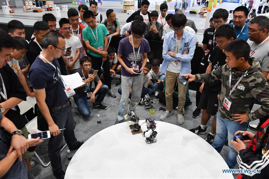 Visitors watch robots competing in boxing at the 20th National Robot and Artificial Intelligence Competition in Shunde District of Foshan, south China\'s Guangdong Province, Oct. 24, 2018. The 20th National Robot and Artificial Intelligence Competition kicked off here on Wednesday. More than 200 teams from 78 Chinese colleges will take part in 49 competitions under 13 categories. (Xinhua/Sadat)