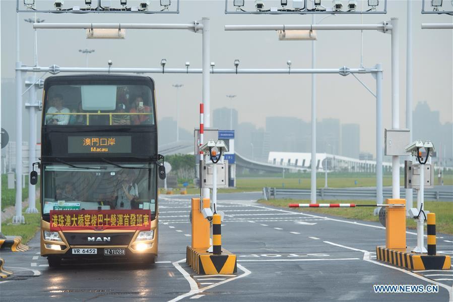 A shuttle bus arrives at the Macao port of the Hong Kong-Zhuhai-Macao Bridge in Macao, south China,Oct. 24, 2018. The Hong Kong-Zhuhai-Macao bridge, the world\'s longest cross-sea bridge, opened to public traffic at 9 a.m. Wednesday. (Xinhua/Cheong Kam Ka)