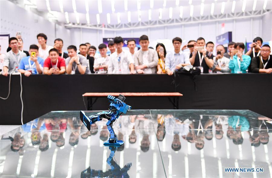 Visitors watch a humanoid robot dancing at the 20th National Robot and Artificial Intelligence Competition in Shunde District of Foshan, south China\'s Guangdong Province, Oct. 24, 2018. The 20th National Robot and Artificial Intelligence Competition kicked off here on Wednesday. More than 200 teams from 78 Chinese colleges will take part in 49 competitions under 13 categories. (Xinhua/Liu Dawei)