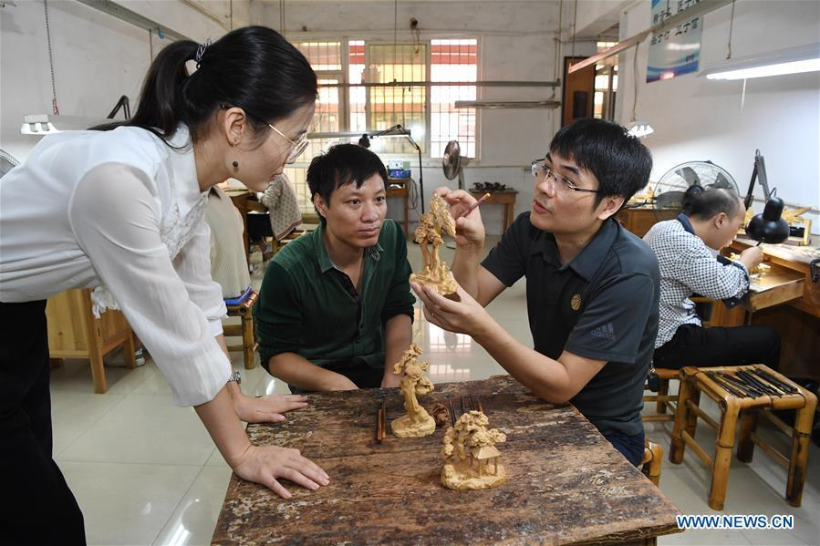 Lin Jianjun (R, front) and Chen Qin check wood carving products at a plant in Putian, southeast China\'s Fujian Province, Oct. 23, 2018. Lin Jianjun, who learnt wood carving at the age of 16, has studied the making skill of this traditional artwork for more than 20 years. In 2014, Lin got married with Chen Qin. The wife was influenced by her husband and got interested in wood carving. She developed the wood carving by combining a traditional skill to make wood carving inlaid with gold and silver. The couple meanwhile try to promote the Putian wood carving by giving lessons, instructing apprentices and displaying their works to the public. In 2018, Lin was appointed as the inheritor of the wood carving skill, a provincial-level intangible cultural heritage. (Xinhua/Jiang Kehong)