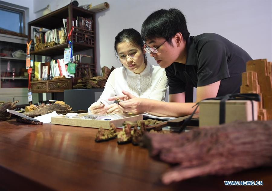 Lin Jianjun (R) and Chen Qin discuss the design of wood carving ornament at their studio in Putian, southeast China\'s Fujian Province, Oct. 23, 2018. Lin Jianjun, who learnt wood carving at the age of 16, has studied the making skill of this traditional artwork for more than 20 years. In 2014, Lin got married with Chen Qin. The wife was influenced by her husband and got interested in wood carving. She developed the wood carving by combining a traditional skill to make wood carving inlaid with gold and silver. The couple meanwhile try to promote the Putian wood carving by giving lessons, instructing apprentices and displaying their works to the public. In 2018, Lin was appointed as the inheritor of the wood carving skill, a provincial-level intangible cultural heritage. (Xinhua/Jiang Kehong)