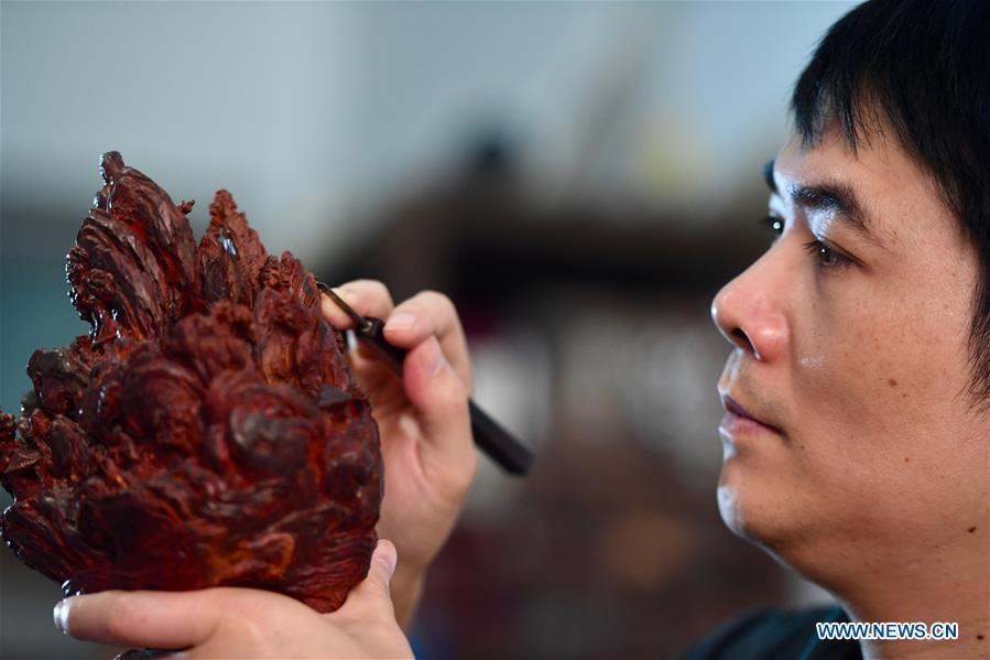 Lin Jianjun makes wood carving at a studio in Putian, southeast China\'s Fujian Province, Oct. 24, 2018. Lin Jianjun, who learnt wood carving at the age of 16, has studied the making skill of this traditional artwork for more than 20 years. In 2014, Lin got married with Chen Qin. The wife was influenced by her husband and got interested in wood carving. She developed the wood carving by combining a traditional skill to make wood carving inlaid with gold and silver. The couple meanwhile try to promote the Putian wood carving by giving lessons, instructing apprentices and displaying their works to the public. In 2018, Lin was appointed as the inheritor of the wood carving skill, a provincial-level intangible cultural heritage.(Xinhua/Jiang Kehong)
