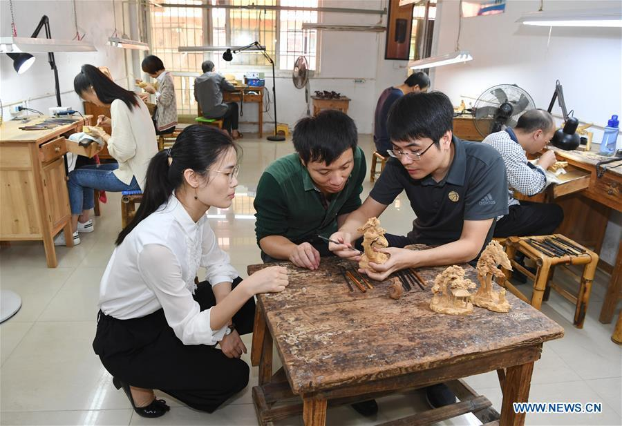 Lin Jianjun (R, front) and Chen Qin (L, front) check wood carving products at a plant in Putian, southeast China\'s Fujian Province, Oct. 23, 2018. Lin Jianjun, who learnt wood carving at the age of 16, has studied the making skill of this traditional artwork for more than 20 years. In 2014, Lin got married with Chen Qin. The wife was influenced by her husband and got interested in wood carving. She developed the wood carving by combining a traditional skill to make wood carving inlaid with gold and silver. The couple meanwhile try to promote the Putian wood carving by giving lessons, instructing apprentices and displaying their works to the public. In 2018, Lin was appointed as the inheritor of the wood carving skill, a provincial-level intangible cultural heritage. (Xinhua/Jiang Kehong)