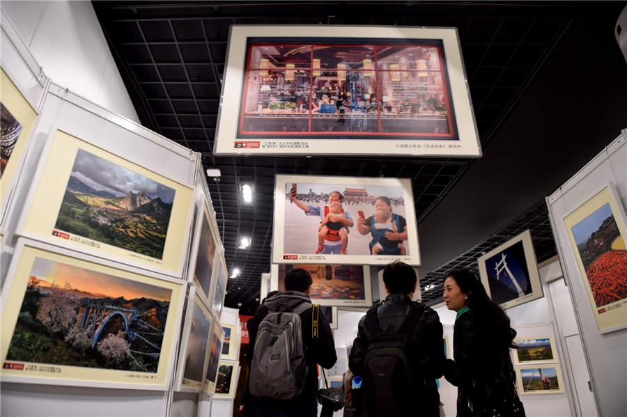 Visitors look at mobile photography works displayed at Photo Beijing 2018 in Beijing, Oct. 20, 2018. (Photo/Xinhua)