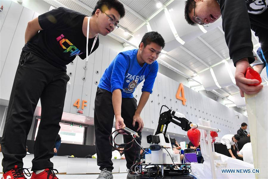 Lao Guihong (C) from Dalian University of Technology adjusts a robot designed for picking at the 20th National Robot and Artificial Intelligence Competition in Shunde District of Foshan, south China\'s Guangdong Province, Oct. 24, 2018. The 20th National Robot and Artificial Intelligence Competition kicked off here on Wednesday. More than 200 teams from 78 Chinese colleges will take part in 49 competitions under 13 categories. (Xinhua/Chen Liqun)