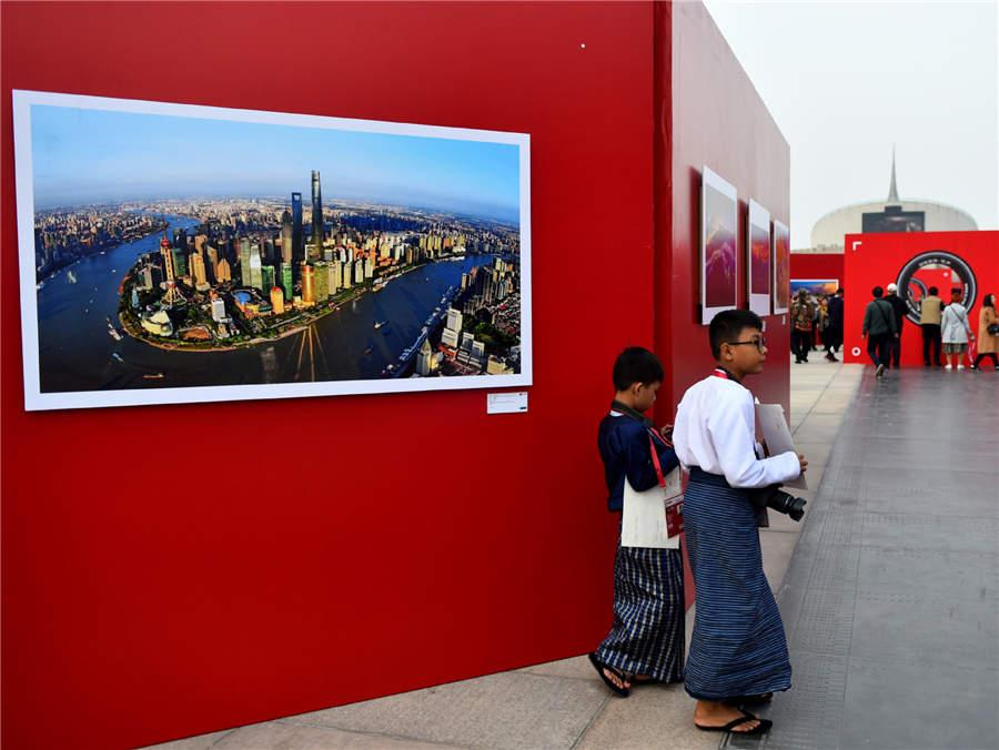 Visitors walk past a photography work displayed at Photo Beijing 2018 in Beijing, Oct. 20, 2018.  (Photo/Xinhua)