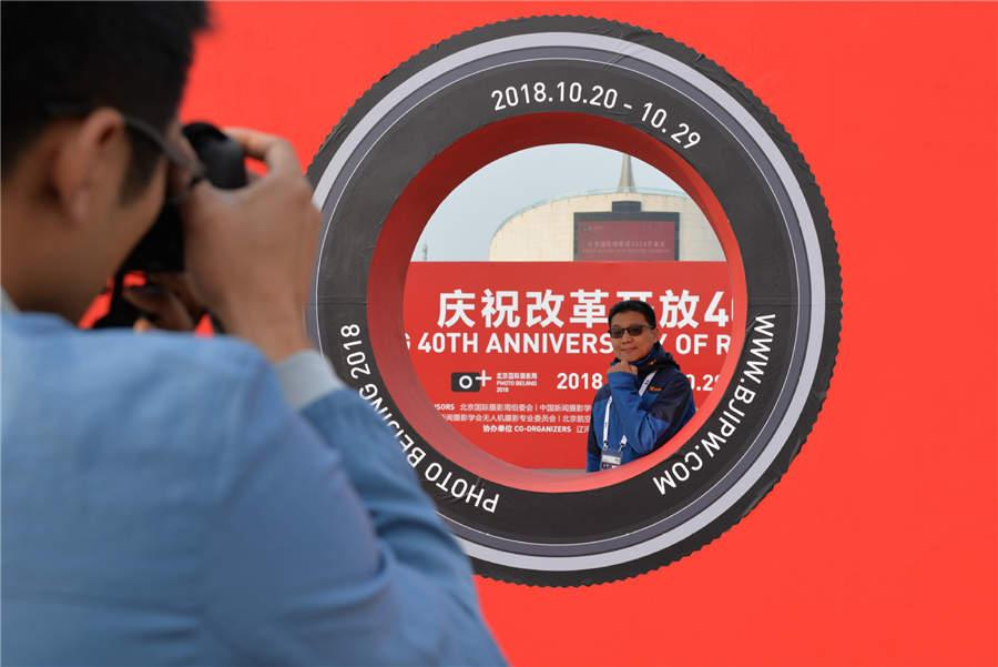 A visitor poses for a photo during Photo Beijing 2018 at the China Millennium Monument in Beijing, Oct. 20, 2018. (Photo/Xinhua)