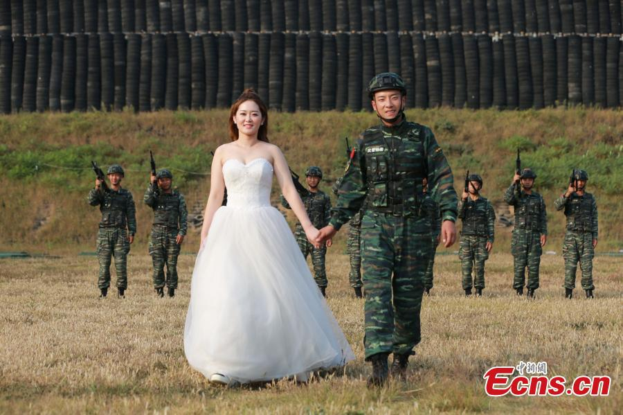 An armed police squad head in Yantai City, East China's Shandong Province and his wife took special wedding photos at a barrack amid cheers and support of other members of the paramilitary police unit. (Photo: China News Service/Yang Lei)