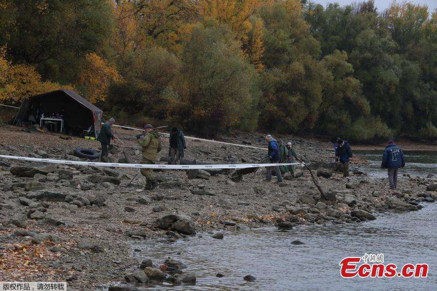 Hungarian archaeologists inspect the site where they found coins from the 16th-17th centuries and special weapons on the banks of the Danube river due to its low water level on October 25, 2018 near Erd, located 25 kilometers from Budapest. According to archaeologists working on site, the treasure comes from a cargo of a commercial ship that probably sank in the 18th century. (Photo/Agencies)