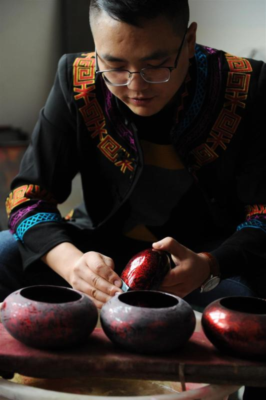 Gao burnishes the lid of a lacquer pot to bring the surface to the highest sheen. (Photo/Xinhua)