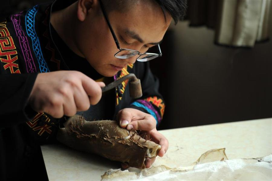 """With patience and painstaking care, Gao begins work on a new piece of lacquerware. Each item needs to go through some 50 processes. (Photo/Xinhua)  Each piece of lacquerware needs to go through some 50 processes and 80 decorative finishes, such as engraving and gilding, and laying on lacquer of a different color.  Lacquerware is often molded on a base of horse or buffalo hide, shaped after being soaked in water before being dried over a fire. The process is not only time-consuming but requires great skill. Only masters with years of experience are up to the task.  Dafang County may be home to one of China's five most highly regarded styles of lacquer, but there has been a drop in output in recent years.   """"Lack of funds and a resultant decline in profit are the major reasons,"""" says Zhang Yu, of the county bureau of industrial economy and energy.  """"But the sophisticated craftsmanship involved in making Dafang lacquerware is incomparable."""""""