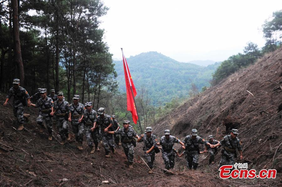 Hand-in-hand, soldiers walk across part of the minefield in the border city of Pingxiang before handing the landmine-free field over to the locals. The PLA soldiers detonated on Thursday, Oct. 25, 2018 the last mine in a minefield in Pingxiang. The operation marked the completion of a years-long landmine-sweeping mission in the Guangxi section of the Sino-Vietnam border, clearing the dangerous historical legacy that has hindered border development. (Photo: China News Service/Jiang Xuelin)