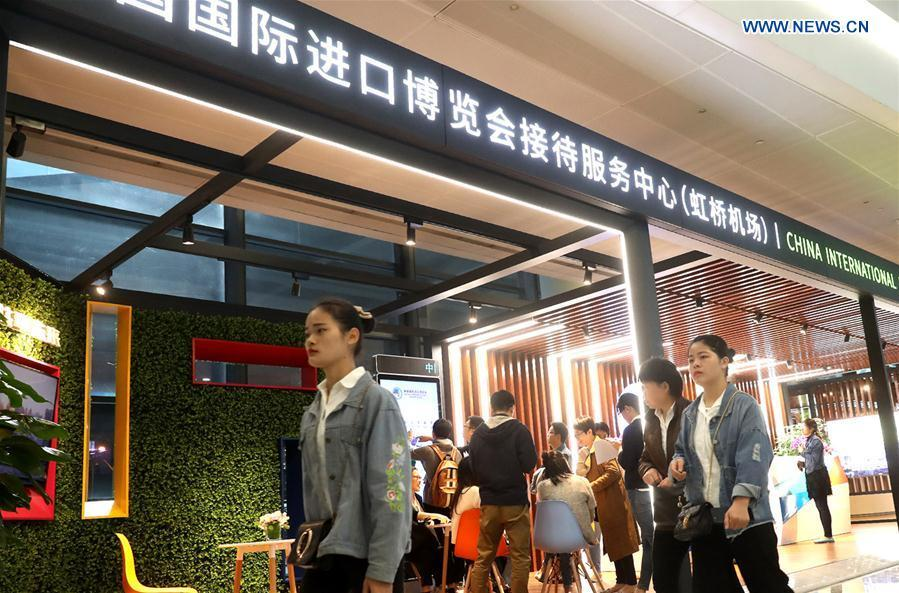 Passengers walk passing a service center for the first China International Import Expo (CIIE) at Pudong International Airport in Shanghai, east China, Oct. 24, 2018. The CIIE will be held in Shanghai on Nov. 5-10. (Xinhua/Chen Fei)