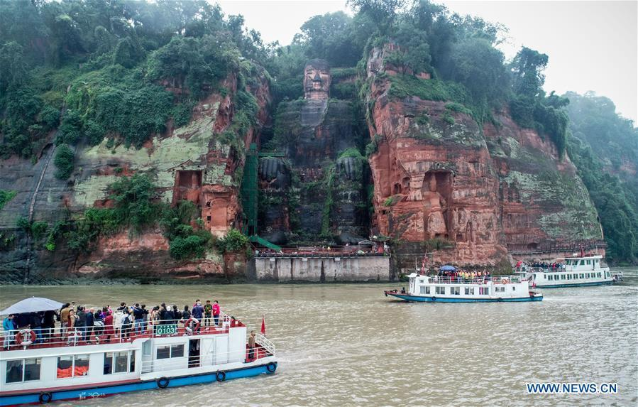 Tourists view the Leshan Giant Buddha on boat in Leshan City, southwest China\'s Sichuan Province, Oct. 19, 2018. The examination of Leshan Giant Buddha started on Oct. 8 to collect data for better restoration. (Xinhua/Chen Minxiang)