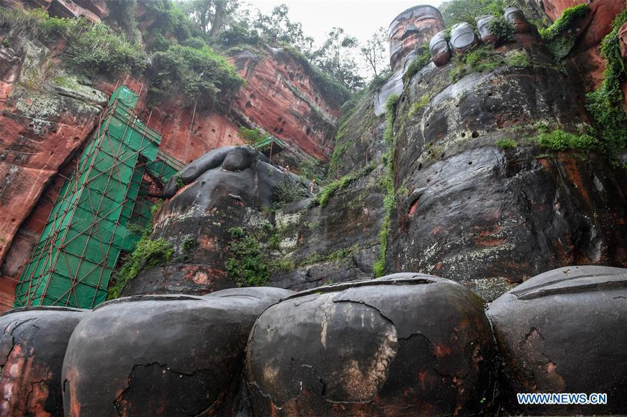 Workers install scaffolds for the examination work of the Leshan Giant Buddha in Leshan City, southwest China\'s Sichuan Province, Oct. 19, 2018. The examination of Leshan Giant Buddha started on Oct. 8 to collect data for better restoration. (Xinhua/Zhang Chaoqun)