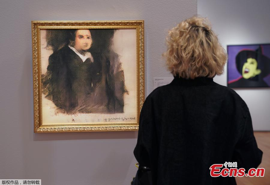 A woman looks at a work of art created by an algorithm by French collective named OBVIOUS which produces art using artificial intelligence, titled \