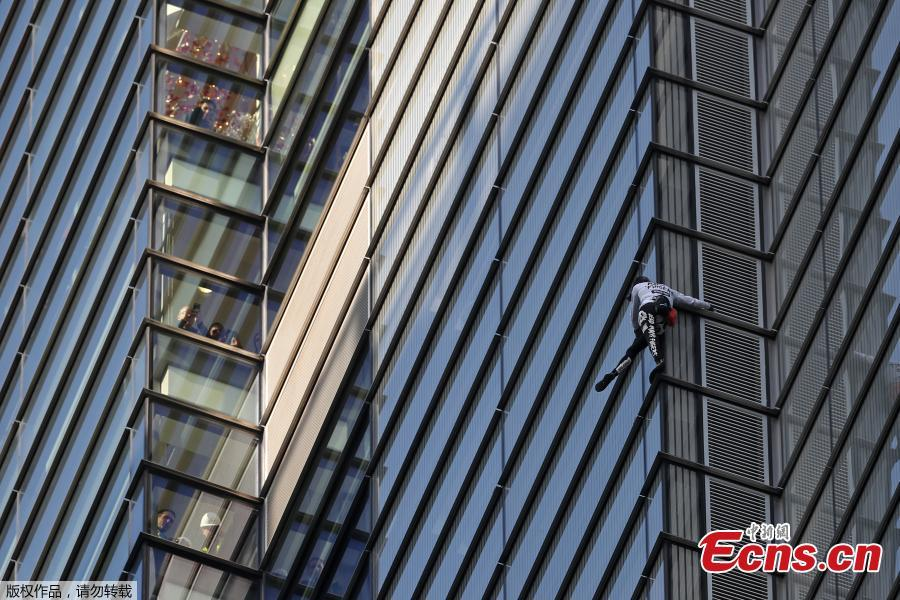 People (L) look out of nearby windows as French urban climber Alain Robert, also known as \