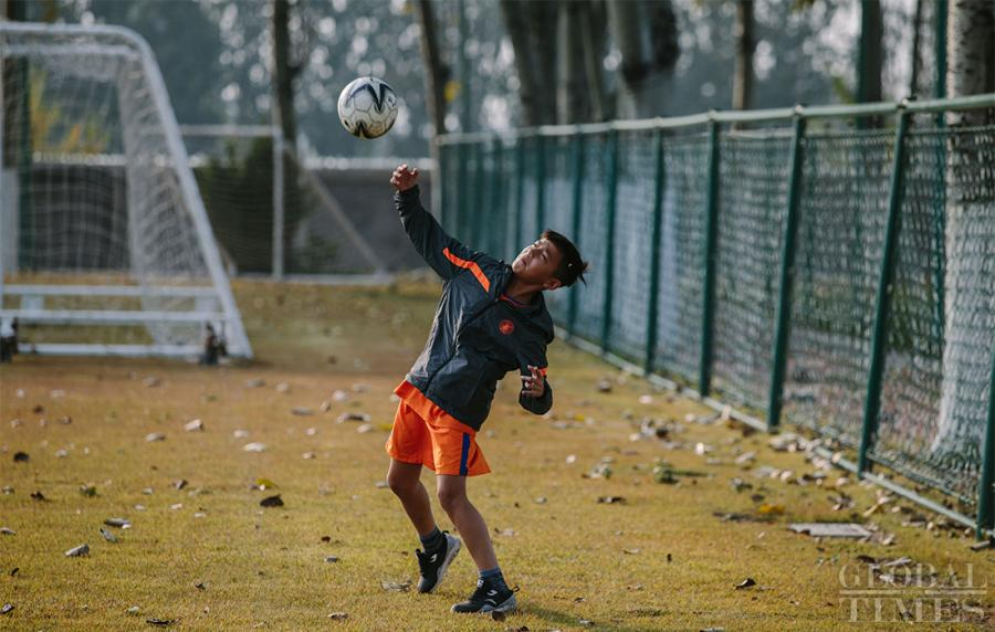 Arpat, 11, warms up on the sidelines as he is unable to participate in the training for the day due to an injury at the Shandong Luneng Taishan Football School on October 24, 2018. (Photo: Li Hao/GT)  The Shandong Luneng Taishan Football School in Weifang, East China's Shandong Province, is the top youth training base in China. Young soccer talents from all around the country are selected to attend the school for training and studying, including more than 20 youths from the Xinjiang Uyghur Autonomous Region. Join us as we take a glimpse of their daily life.