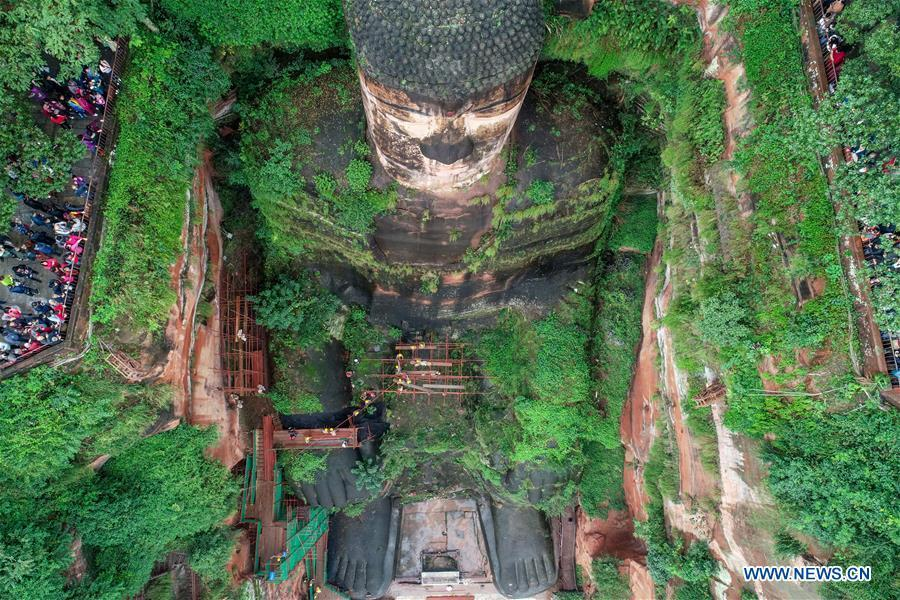 Tourists view the Leshan Giant Buddha in Leshan City, southwest China\'s Sichuan Province, Oct. 19, 2018. The examination of Leshan Giant Buddha started on Oct. 8 to collect data for better restoration. (Xinhua/Chen Minxiang)
