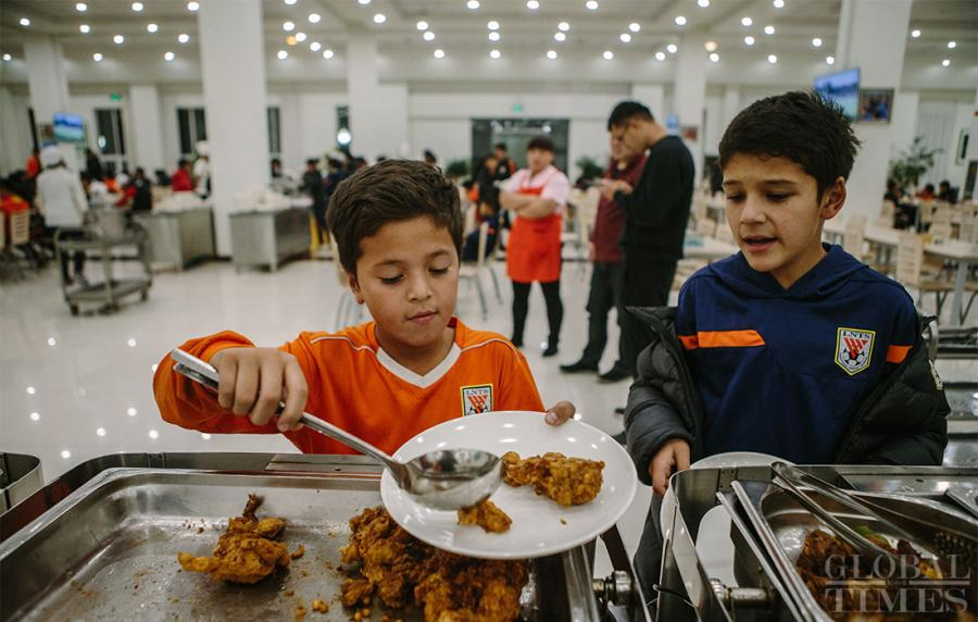 Young soccer players fill their plates for dinner at the school\'s mess hall. (Photo: Li Hao/GT)
