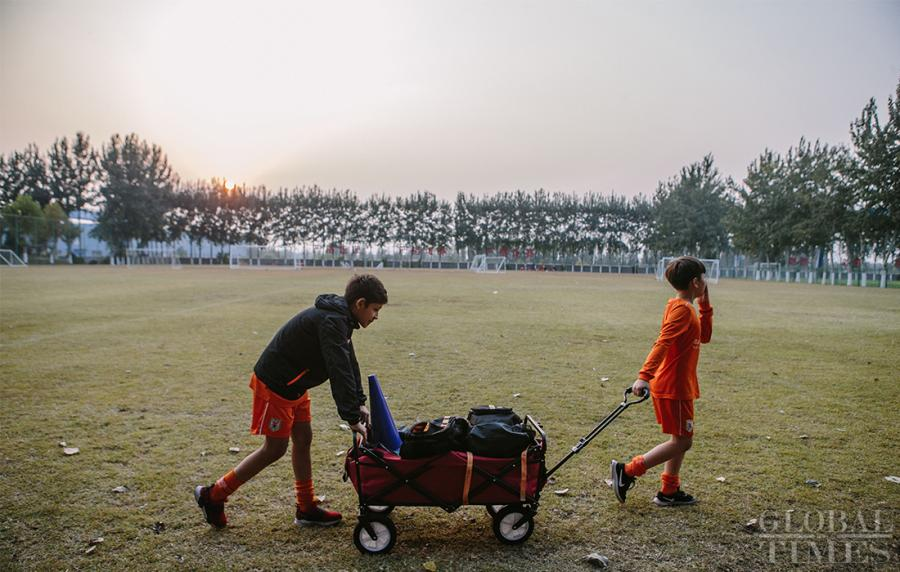 Two young players return the training equipment to the warehouse after training at the Shandong Luneng Taishan Football School in Weifang, East China\'s Shandong Province, on October 24, 2018.  (Photo: Li Hao/GT)