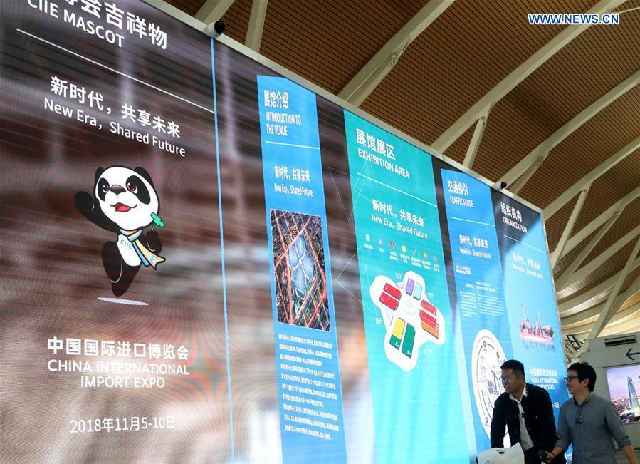 Passengers walk passing a LED screen playing promotion videos for the first China International Import Expo (CIIE) at Pudong International Airport in Shanghai, east China, Oct. 25, 2018. The CIIE will be held in Shanghai on Nov. 5-10. (Xinhua/Chen Fei)