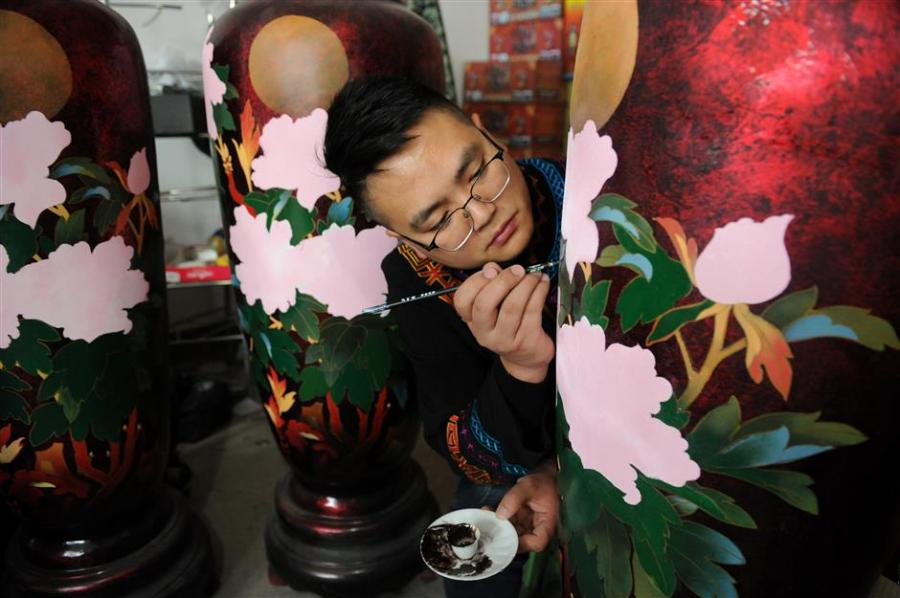 """Gao Yan adds the finishing flourishes to a lacquer vase. Gao is a master of Dafang lacquerware, an irresistible part of China\'s cultural heritage. (Photo/Xinhua)  """"We are working to increase investment and seeking cooperations to ensure the art form's survival,"""" he adds.  Che Dan, director of the Dafang office of cultural industry, says, """"Traditional skills and concepts need to seek new opportunities like combining lacquerware with modern furniture.  """"There is also potential to expand consumption in through tourism."""""""
