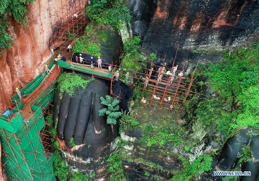 Workers install scaffolds for the examination work of the Leshan Giant Buddha in Leshan City, southwest China\'s Sichuan Province, Oct. 19, 2018. The examination of Leshan Giant Buddha started on Oct. 8 to collect data for better restoration. (Xinhua/Chen Minxiang)