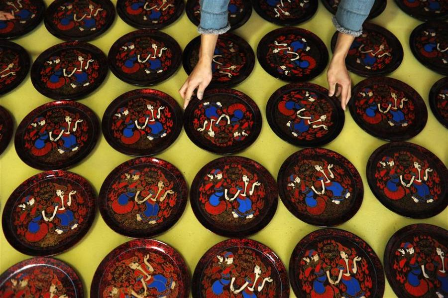 """Newly painted lacquer plates are laid out for natural drying at the High Sheen Yi-ethnic Style Lacquerware Factory in Dafang County, southwest China\'s Guizhou Province.  (Photo/Xinhua)  Regarded as one of """"the three specialties of Guizhou"""" along with the bamboo flute and the province's signature white wine, Dafang lacquerware is known  over the world for its delicacy and beauty.  The history of the art form can be traced back more than 600 years to when a sophisticated process was developed during Ming Dynasty (1368-1644)."""