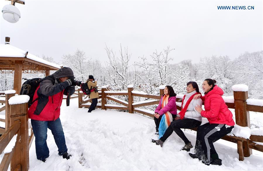 People enjoy the snow scenery at a scenic spot in Oroqen Autonomous Banner of Hulun Buir, north China\'s Inner Mongolia Autonomous Region, Oct. 26, 2018. A snowfall hit Oroqen Autonomous Banner of Hulun Buir on Friday.(Xinhua/Hou Yupeng)