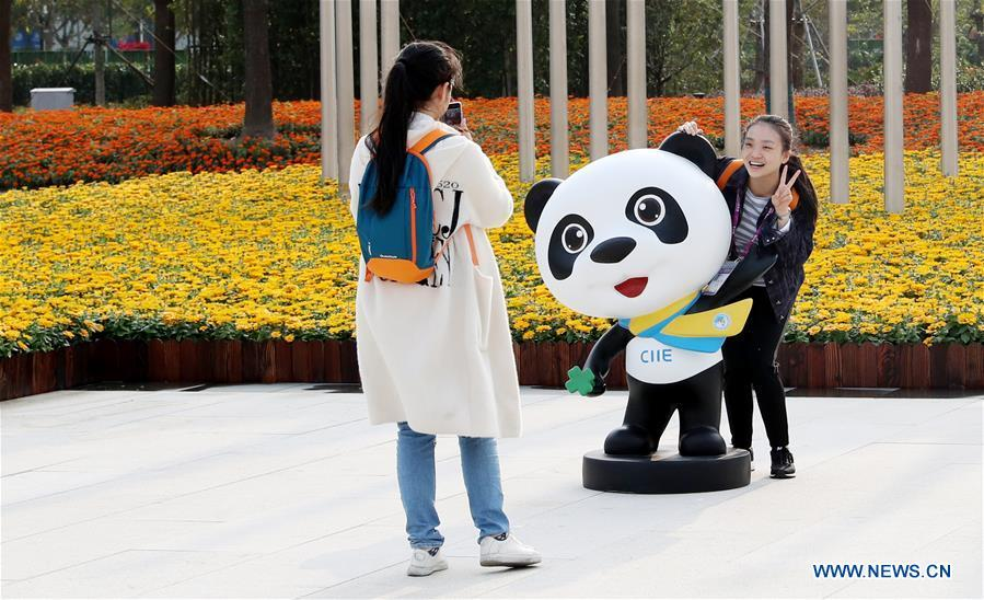 A volunteer for the upcoming China International Import Expo (CIIE) poses for a photo with the mascot \