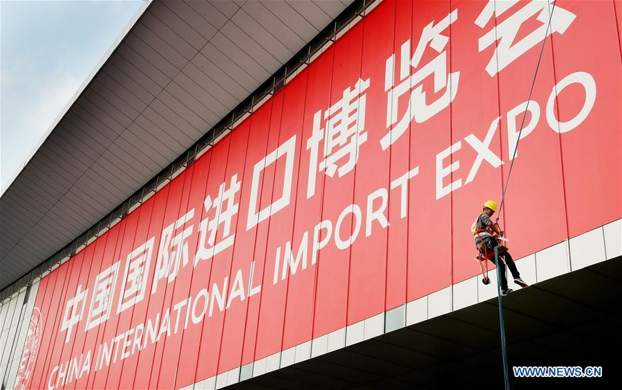 A worker pastes a sign poster for the upcoming China International Import Expo (CIIE) at the National Exhibition and Convention Center in Shanghai, east China, Oct. 26, 2018. The exhibition booth arrangement work for the CIIE has begun in Shanghai, the organizer said Thursday. Over 1,800 exhibition booths will be set up by the end of the month, before exhibitors start to display products on Nov. 1 and 2, according to the China International Import Expo Bureau. (Xinhua/Fang Zhe)
