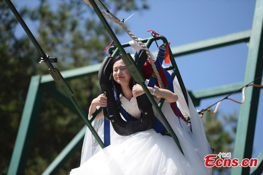 A woman dons a wedding dress to pose for a photo while sitting on a swing that is built close to a cliff at the Shiniuzhai National Geological Park in Pingjiang County, Central China\'s Hunan Province, Oct. 28, 2018. (Photo: China News Service/Yang Huafeng)