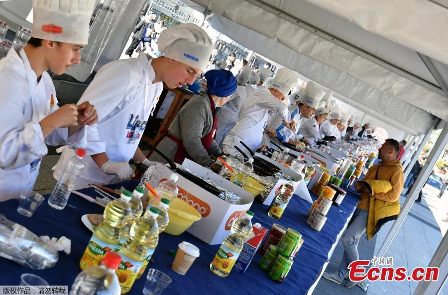 Bosnian chefs serve pancakes while they plan to break Guinness record by making and serving 13,000 pancakes in 8 hours in Sarajevo, Bosnia and Herzegovina, Oct. 26, 2018. A team of Balkan chefs rustled up a world record number of a pancakes on Friday, making 14,186 in eight hours at Sarajevo's tourist fair. The existing official record of 12,716 pancakes was set in Moscow in 2017. (Photo/Agencies)