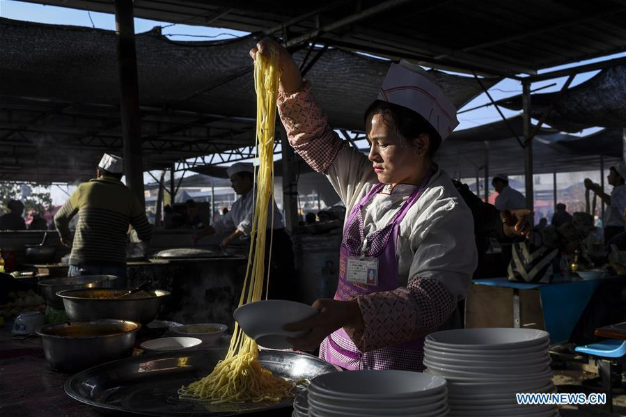 A vender makes noodles at a Sunday bazaar in Bachu County, northwest China\'s Xinjiang Uygur Autonomous Region, Oct. 28, 2018. (Xinhua/Hu Huhu)