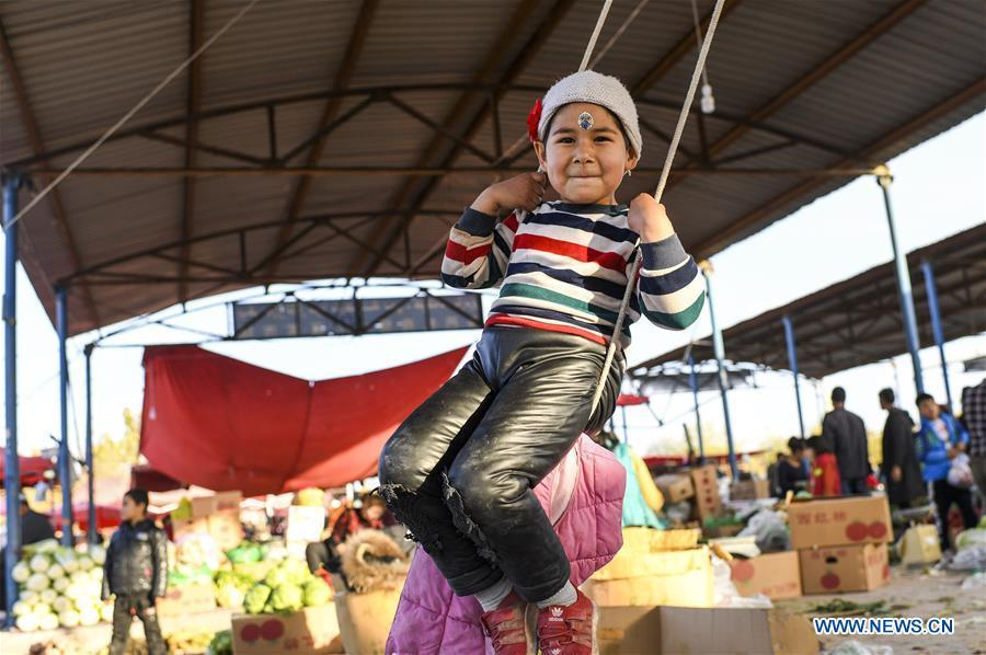 <?php echo strip_tags(addslashes(A girl plays a swing at a Sunday bazaar in Bachu County, northwest China's Xinjiang Uygur Autonomous Region, Oct. 28, 2018. (Xinhua/Hu Huhu))) ?>