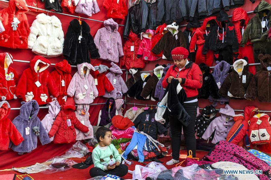 A vender sells clothes at a Sunday bazaar in Bachu County, northwest China\'s Xinjiang Uygur Autonomous Region, Oct. 28, 2018. (Xinhua/Hu Huhu)